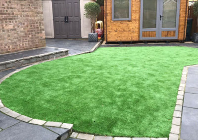 Black Indian Sandstone with grey cobble edging and astro turf